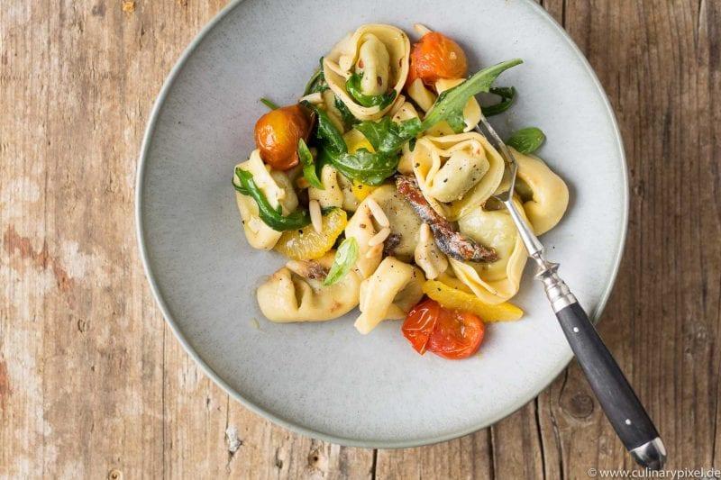 Tortellini mit Rucola, Tomaten, Orangenfilets und Sardellen