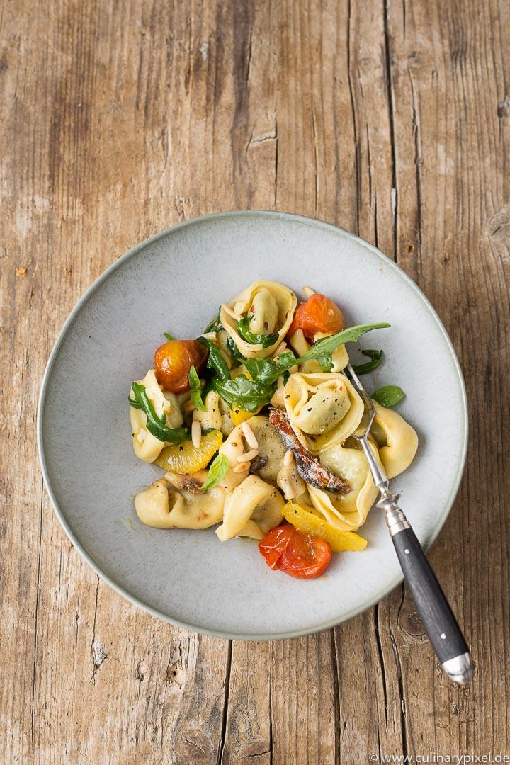 Tortelloni mit Rucola, Tomaten, Orangenfilets und Sardellen